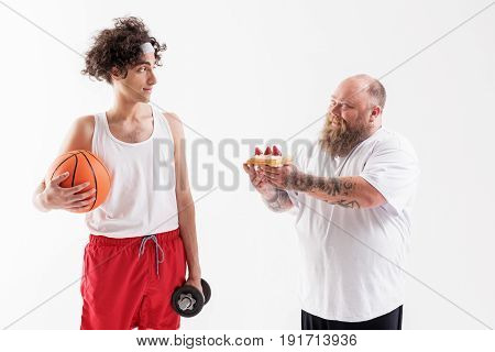 Eat unhealthy food and be like me. Confident fat man is proposing sweet dessert to young skinny boy. Boy is holding ball and dumbbell and looking at fatso with mistrust. Isolated