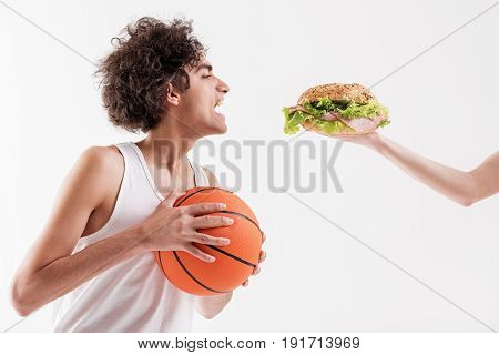 Starving skinny male basketball player is opening his mouth widely while looking at appetite sandwich in female arm. Isolated