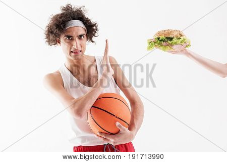 Slim young man is refusing to eat unhealthy food. He is raising hand opposite burger and looking at camera with aversion. Guy is holding ball. Isolated