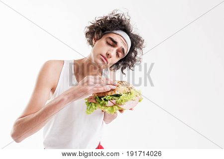 Hungry thin young man is enjoying smell of appetite sandwich. His eyes are closed with pleasure. Isolated and copy space