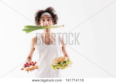I have already made my choice. Shocked young skinny man is standing with healthy onion in his mouth. He is holding sweet dessert and sandwich. Isolated and copy space