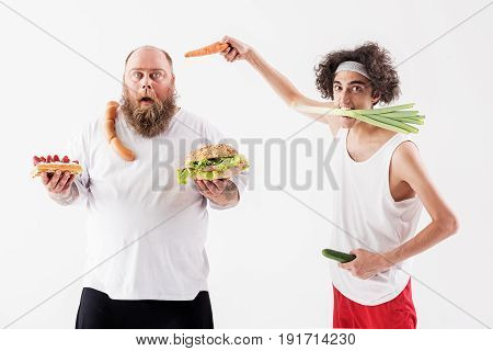 Look at him. Hungry thin young guy is pointing carrot at shocked fat man. He is keeping onion in mouth while fatso is holding unhealthy food. Isolated