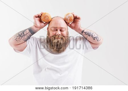 Joyful male fatso is having fun with sweet buns. He is raising donuts as ears and smiling. His eyes are closed. Isolated