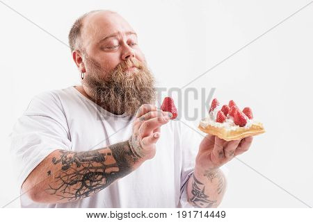 Lets put you on your place. Relaxed male fatso is putting strawberry on cream cake with serenity. Isolated
