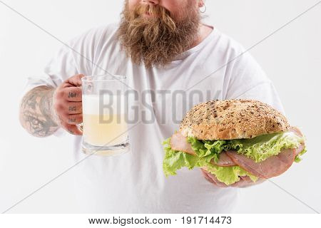 Joyful thick guy is holding cold alcohol beverage and unhealthy food. He is standing and smiling. Focus on burger and glass of lager