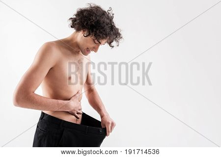 Wonderful result after diet. Joyful slender guy is looking at his abdomen with satisfaction while holding large trousers. He is standing and smiling. Isolated and copy space