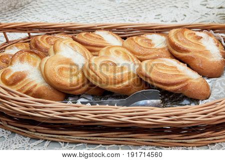 Baked buns with sugar in wicker basket.