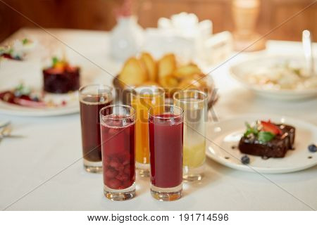 Several kinds of fruit beverages in glasses and cakes on table, shallow dof.