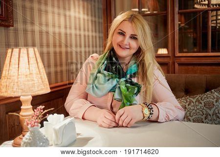 Young blond woman sits at table in cosy cafe.