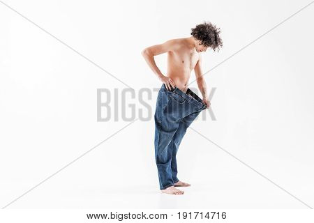 I finally loss weight. Confident thin young man is standing in oversized jeans and looking at his waist with surprise. Isolated and copy space