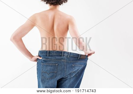 Close up of male thin back standing in large pants. Boy is stretching trousers to show his weight loss. Isolated and copy space