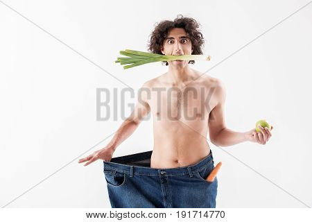 Stick to the diet and be slim like me. Skinny young man is keeping onion in his mouth. He is stretching oversized jeans and looking at camera with shock. Isolated and copy space