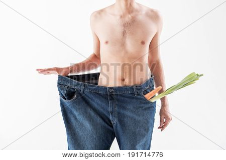 Eat healthy food and be slim. Close up of thin male body wearing large pants. Vegetables are in pockets. Isolated