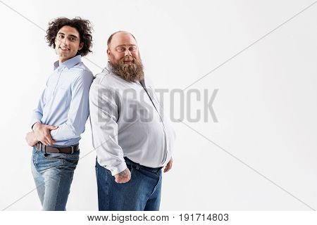 Different but happy. Portrait of joyful slim boy is standing and leaning back on fat bearded man. They are looking at camera and smiling. Isolated and copy space