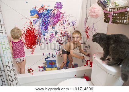 Portrait of two cute adorable white Caucasian little boy and girl toddlers playing painting in bathroom on walls having fun lifestyle active childhood concept early education development