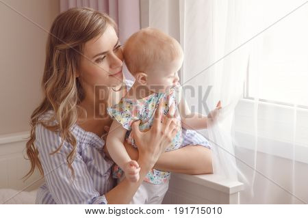 Closeup portrait of beautiful white Caucasian woman mother with cute adorable blonde baby girl daughter with large blue eyes sitting on bed near window together candid family lifestyle