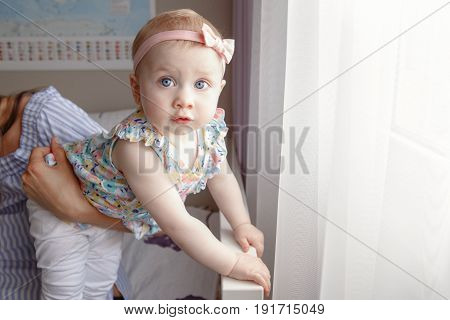 Closeup portrait of beautiful white Caucasian cute adorable blonde baby girl daughter with large blue eyes standing on bed near window in mothers hands looking in camera candid family lifestyle