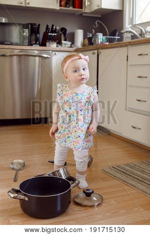 Portrait of cute adorable funny little Caucasian blonde baby girl playing in kitchen with utensils pot and ladle child with funny face emotional expression happy childhood concept