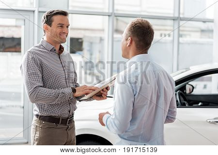 Side view smiling male discussing contract with salesman in automobile showroom