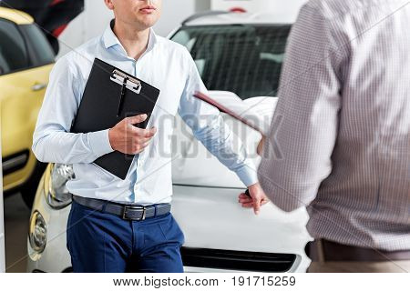 Serene agent speaking with client while standing in automobile showroom