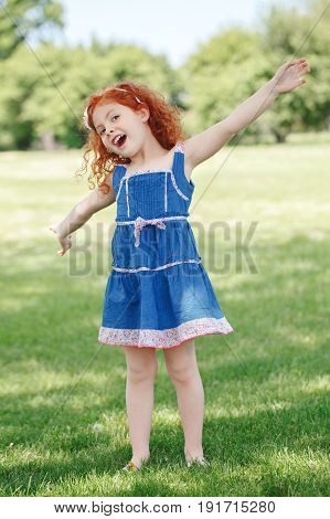 Portrait of cute adorable little red-haired Caucasian girl child in blue dress standing in field meadow park outside playing singing having fun happy lifestyle childhood concept