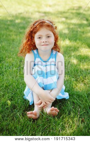 Portrait of cute adorable little red-haired Caucasian girl child in blue dress sitting in field meadow park outside looking in camera having fun happy lifestyle childhood concept