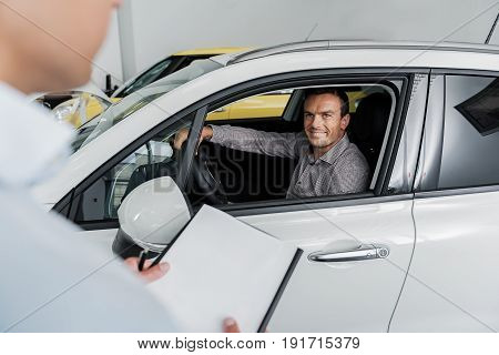 Cheerful buyer sitting in modern vehicle while speaking with agent in automobile showroom