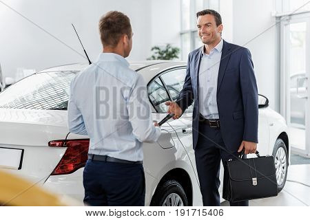 Outgoing businessman speaking with agent while standing near new vehicle in automobile showroom
