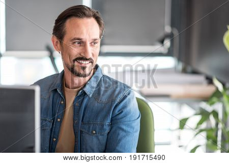 Cheerful male worker is sitting at workplace and looking aside with wide smile. Portrait. Copy space on right side