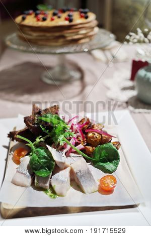 Herring, potato, vegetables on plate, sweet pie out of focus on table