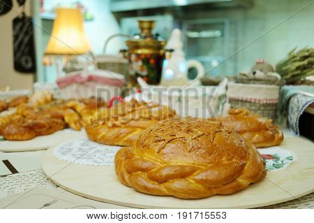 Bread loafs on table in russian traditional cafe with samovar out of focus