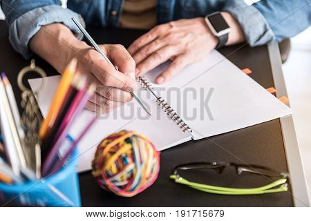 Manager is holding pencil above open notepad and ready to make notes. Close up of male hands keeping pen