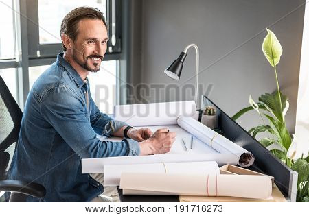 Cheerful man is sitting near workplace, full of various drafts and looking aside with affable smile. He holding pencil. Portrait