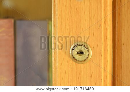 keyhole on door of wooden bookcase in home