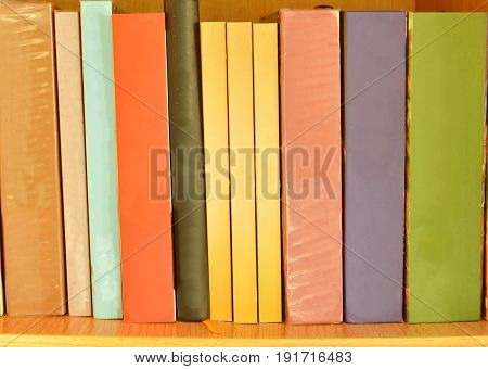 colorful book arrange on the wooden shelf