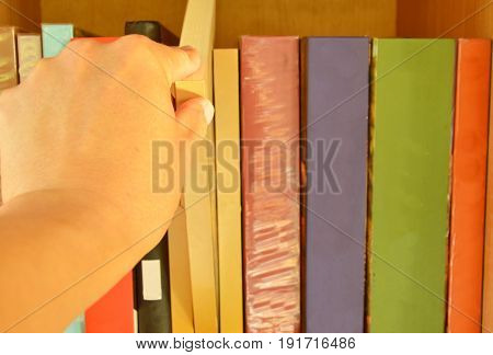 hand choose book to read from wooden shelf