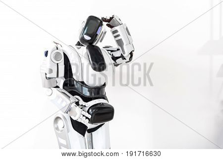 I have to serve people. Robot standing and putting one hand on head. Isolated and copy space