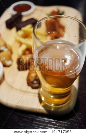Big glass og beer and snaks (smoked meat, French fries, croutons) on wooden table