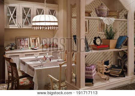 Serving on table with tablecloth in empty home-style restaurant with lampshade, shelves