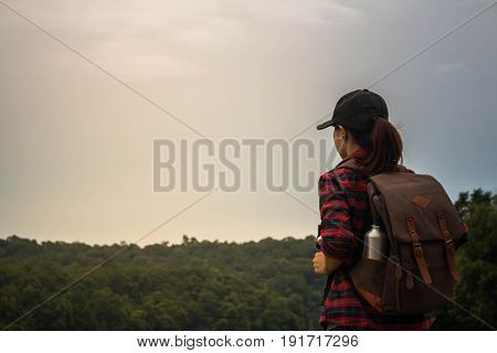 Woman with backpack walking in the mountains by the riv.