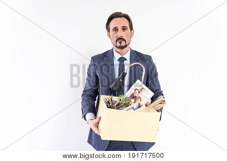 Black stripe. Portrait of disappointed gloomy businessman is standing with his belongings and feeling upset because being fired. He is looking at camera with frustration. Isolated background