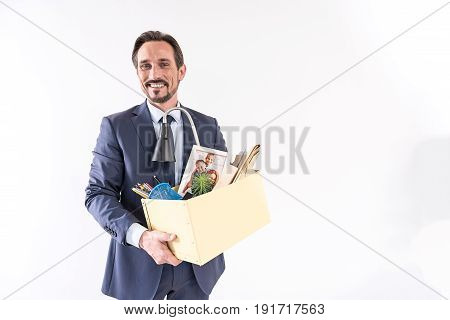 Career ladder. Portrait of positive worker is holding box with belongings and expressing happiness while getting ready to work in new team. He is looking at camera with joy. Isolated with copy space
