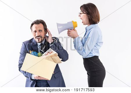 Angry boss. Business woman is yelling through megaphone on dismissed employee who is standing with box and expressing upset. Isolated background