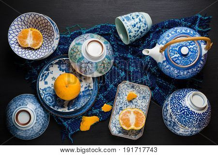 Whole And Slice Oranges Fruits On Ceramic Plate Over Black Wooden Table. Top View.