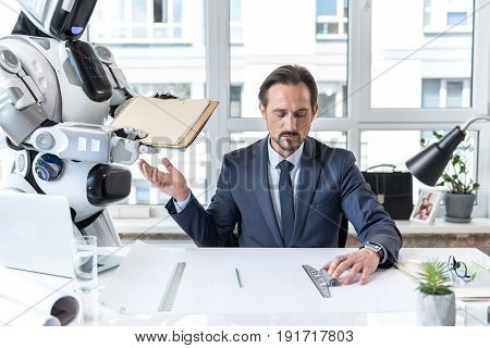 New generation. Portrait of gloomy serious mature man is sitting at table and working while reached out his hand to papers which robot is giving him