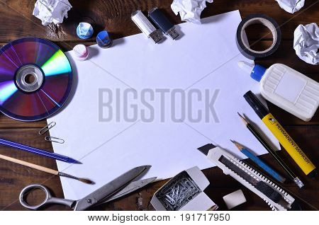 A School Or Office Still Life With A White Blank Sheet Of Paper And Many Office Supplies. The School