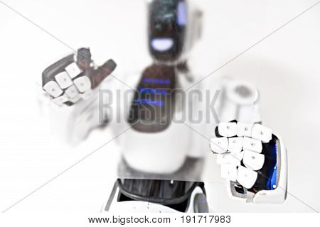 One touch technology. Concentrated cyborg is standing with modern gadgets while touching transparent screen. Selective focus on hands. Isolated background