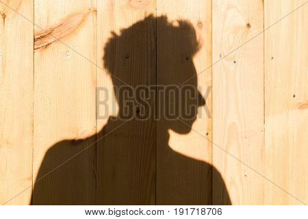 The shadow of a man with spiky hair on the background of wooden wall
