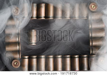 Beautifully Laid Out Shells Of 9 Mm Pistol In A Frame, Covered With Smoke