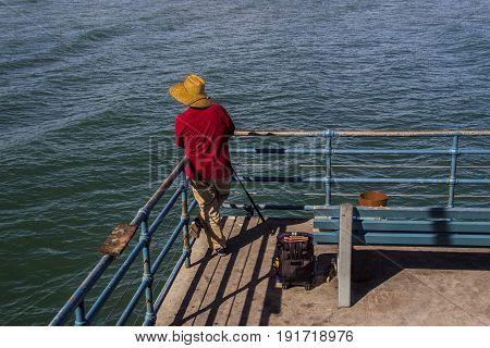 Man wearing red shirt fishing off pier with fishing rod